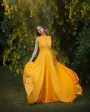 Woman in fluttering yellow long dress under a blossoming tree with yellow flowers, waving silk cloth, artistic