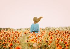 Woman with fly-away hair standing in flower meadow. Unrecognizable brunette woman with fly-away hair standing in red poppy flower meadow in windy weather in stock photo