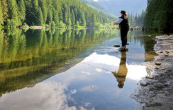 Woman fly fishing at a lake stock photo