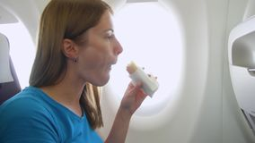 Woman flying in airplane. Female eating sandwich and drinking wine near window during turbulence. Woman flying in airplane in daytime. Hungry female eating stock video