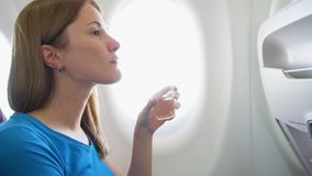 Woman flying in airplane in daytime. Thirsty female drinking wine near window during turbulence. Woman flying in airplane in daytime. Thirsty female drinking stock video footage