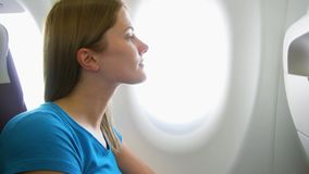 Woman flying in airplane in daytime. Tired by jet lag female relaxing near window during turbulence. Young woman flying in airplane in daytime. Tired by jet lag stock footage
