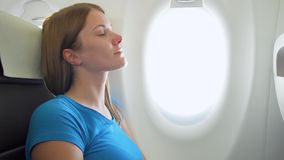 Woman flying in airplane in daytime. Tired by jet lag female relaxing near window during turbulence. Young woman flying in airplane in daytime. Tired by jet lag stock video footage