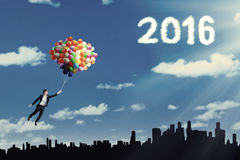 Woman flying with balloon and numbers 2016 Stock Photo