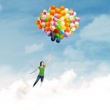 Woman flying with balloons Royalty Free Stock Photography