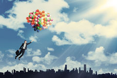 Woman flying with balloons to get her dream 1 Stock Photography