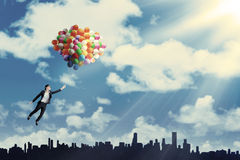 Woman flying with balloons to get her dream Royalty Free Stock Photo