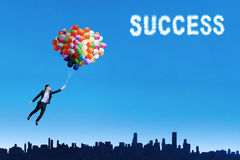 Woman flying with balloons to get her success Royalty Free Stock Photo