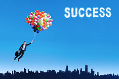 Woman flying with balloons to get her success 1 Stock Images