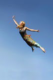 Woman Flying Through Blue Sky Stock Photo