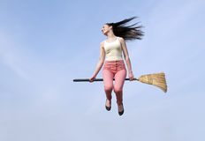 Woman flying with broom Stock Images