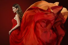 Woman Flying Dress, Elegant Fashion Model in Fluttering Red Gown. Beautiful Girl and Waving Silk Fabric Royalty Free Stock Image