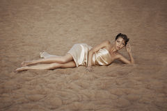 Woman in flying gold cloth. Picture of woman in flying gold cloth in the sand Stock Photo