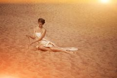 Woman in flying gold cloth. Picture of woman in flying gold cloth in the sand Stock Photos