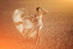 Woman in flying gold cloth. Picture of woman in flying gold cloth in the sand Stock Images