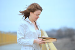 Woman with flying hair with book Stock Photography