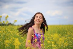 Woman with flying hair on yellow rape field Royalty Free Stock Images