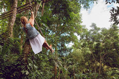 Woman flying high on rope swing on wild jungle background. Family travel lifestyle. Happy young woman flying high with fun on rope swing on wild jungle Stock Images