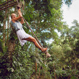 Woman flying high on rope swing on wild jungle background. Family travel lifestyle. Happy young woman flying high with fun on rope swing on wild jungle Stock Image