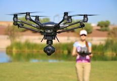 Woman Flying High-Tech Camera Drone (Large File). Picture of a woman flying a professional grade camera drone (UAS UAV Vector Illustration