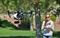 Woman Flying High-Tech Camera Drone. Picture of a woman flying a professional grade camera drone (UAS Stock Photo