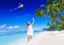 Woman Flying a Kite on the Beach Royalty Free Stock Image