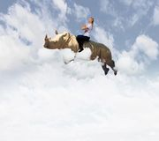 Woman flying rhino Stock Images