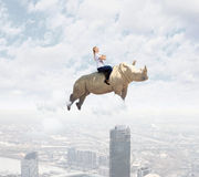 Woman flying rhino Royalty Free Stock Photo