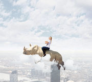 Woman flying rhino Royalty Free Stock Photos