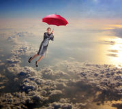 Woman flying in the sky with umbrella Stock Photo