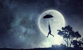Woman flying on umbrella . Mixed media royalty free stock photo