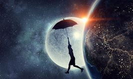 Woman flying on umbrella . Mixed media royalty free stock images