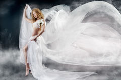 Woman with flying white fabric. Beautiful woman walking with flying white chiffon fabric, waving  as wings on a wind flow. Mysterious fantasy background Royalty Free Stock Photography
