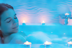 Woman in foam bath with candles. Close up Low light ambient portrait of woman enjoying foam bath.Blue ambient with decorative candles along bath tub stock photography