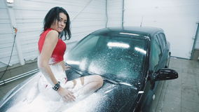 Woman in a foam posing on the hood of the car stock video