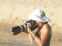 Woman focus with camera in sun. Woman taking pictures with camera wearing white hat in bright sunshine Royalty Free Stock Photos