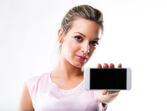 Woman (in focus) holding a mobile phone (out of focus) Royalty Free Stock Images