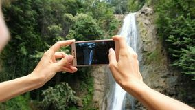 Woman focuses on the phone screen and takes a photo of the waterfall close-up stock video