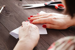 Woman fold sheet of paper while do origami Royalty Free Stock Images