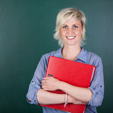 Woman With Folder In Front Of Chalkboard Stock Image