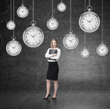 Woman with folder and many clocks stock photography