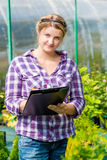 Woman with a folder of readings recorded growth of plants. In the greenhouse Stock Photography