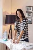 Woman folding clean ironed shirt. On the ironing board after doing the ironing royalty free stock photos