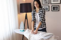 Woman folding clean ironed shirt. On the ironing board after doing the ironing stock images
