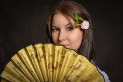 A woman folding fan. A beautiful girl holds a fan Royalty Free Stock Photography