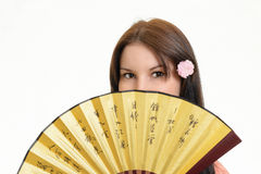 A woman folding fan. A beautiful girl holds a fan Royalty Free Stock Photo