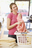 Woman Folding Laundry. A young woman is folding laundry and smiling at the camera.  Vertical shot Stock Photography