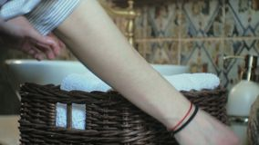 Woman folds clean soft towels in the basket, cleaning concept stock video