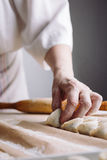 Woman folds the raw dumplings on a sheet of parchment Stock Image