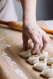 Woman folds the raw dumplings on a sheet of parchment Stock Photo